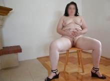 Grosse assise sur une chaise, toute nue