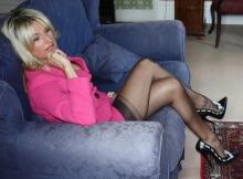 Femme mûre sexy (50 ans) : bourgeoise assise sur son canapé