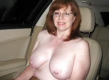 Femme mûre exhibe ses seins en voiture