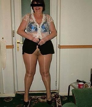 Femme ronde en mini-jupe ouverte en collants