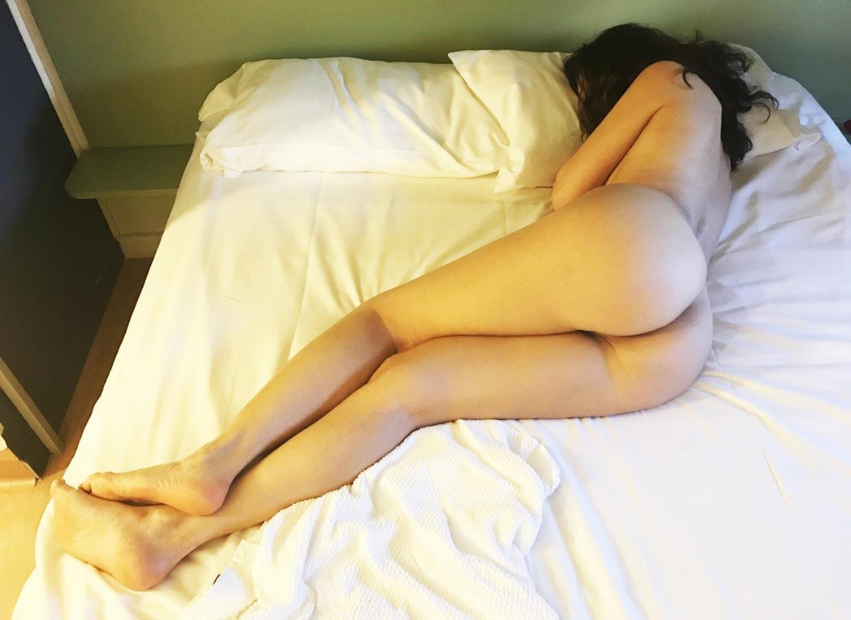 Nora allongée sur le lit de l'hôtel, est une charmante beurette qui propose un plan cul discret à Nanterre.