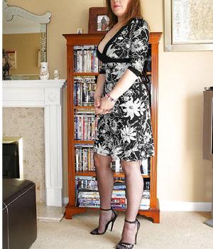 Femme mûre chic et sexy en robe et collants