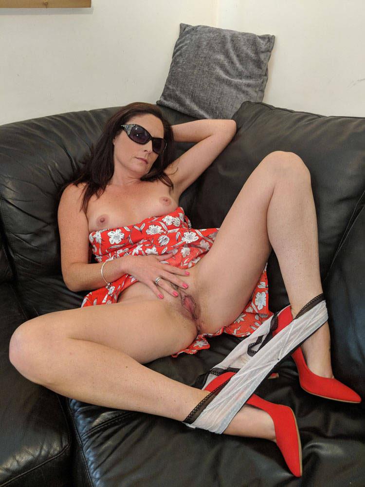 Aline du Mans caresse son petit minou, assise sur le canapé