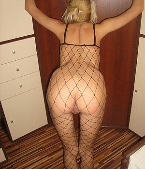 Blonde exhibe ses fesses en combinaison sexy à résilles