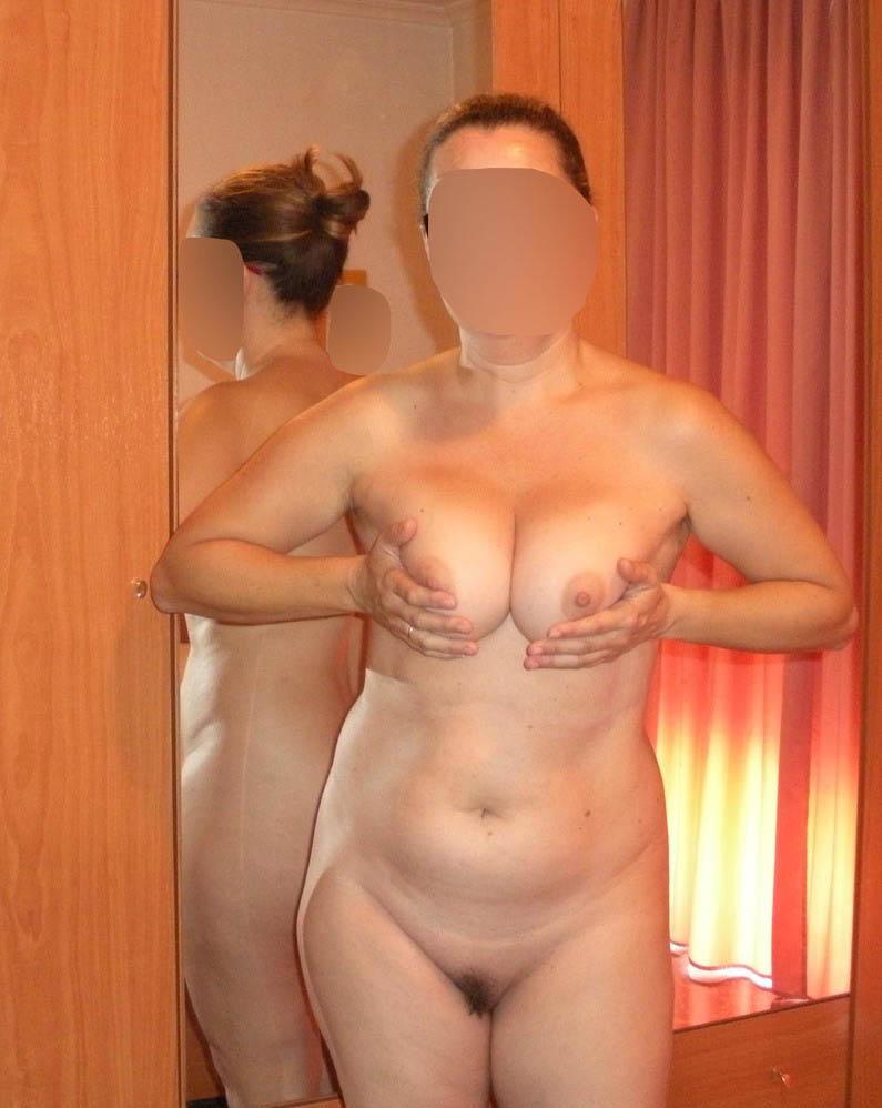 Je serre mes seins, toute nue à la maison