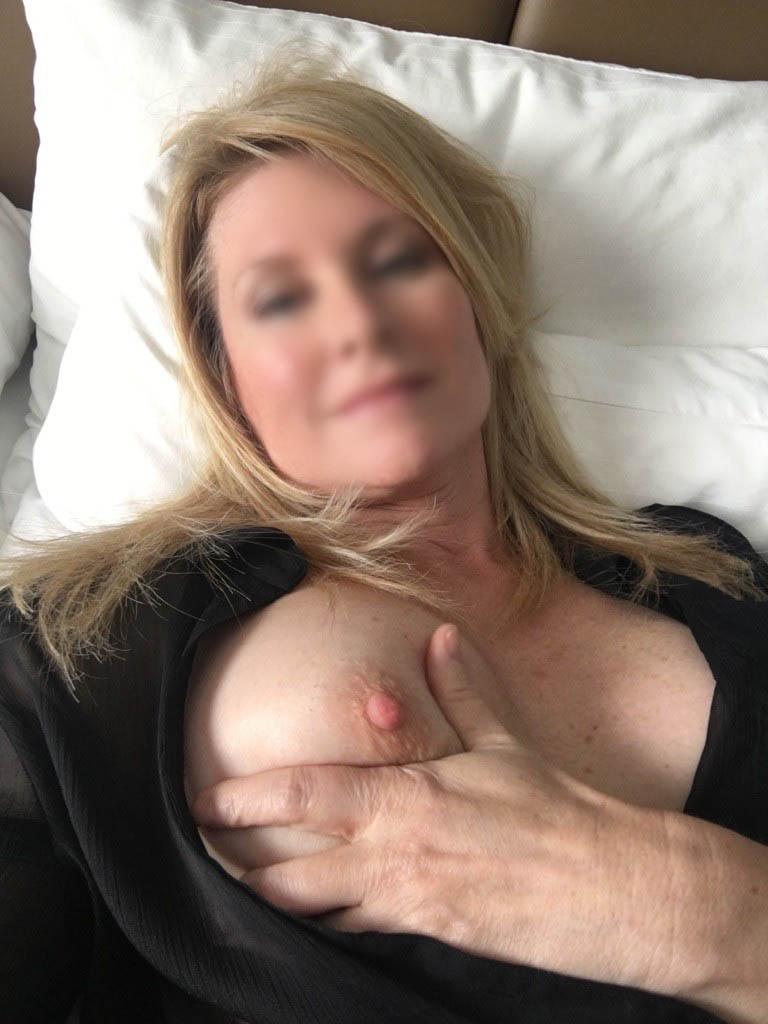 Femme mûre, blonde, montre ses  seins