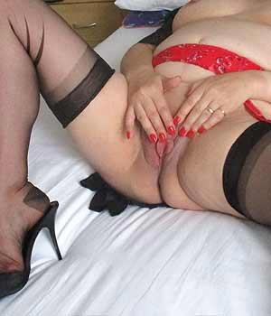 Vieille caresse sa chatte dans le lit en lingerie sexy